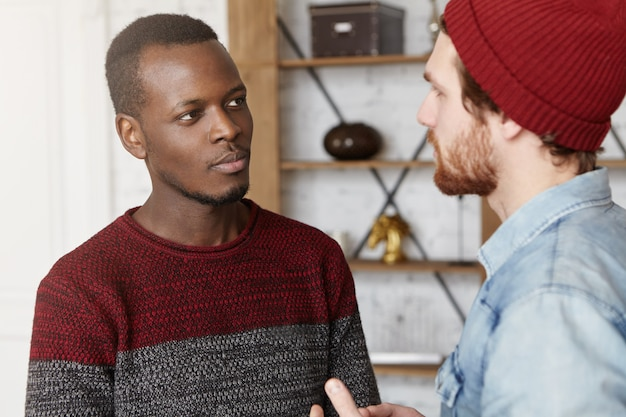 Interracial friendship, people, youth and happiness. stylish bearded hipster in hat explaining something while having conversation or dispute with his african american friend dressed in sweater