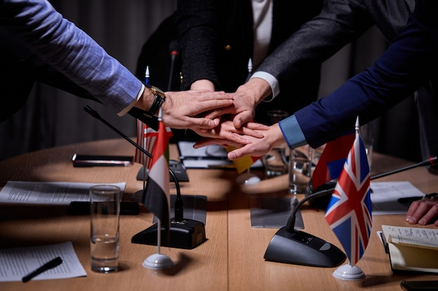 Interracial group of cropped executives holdng hands together, successful work, sign an agreement. in office