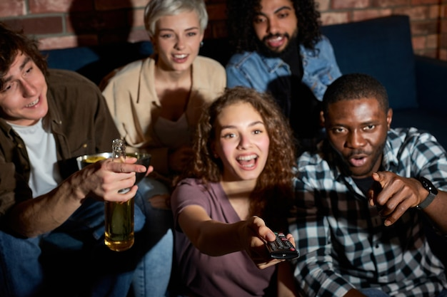 Interracial group of friends discuss which movie to watch, sitting on sofa at home, choosing the most interesting film, relaxed people have talk, switch channels. focus on hands with remote controller