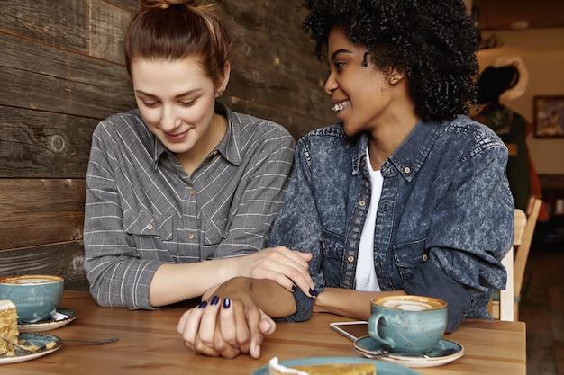Coppie lesbiche felici interrazziali che si rilassano al caffè