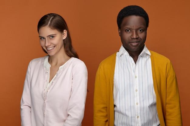 인종 혼혈 관계, 사랑, 우정 및 파트너십 개념. 그녀의 아프리카 남성 동료와 함께 포즈를 취하는 넓은 미소로 행복 확신 젊은 유럽 여자의 초상화