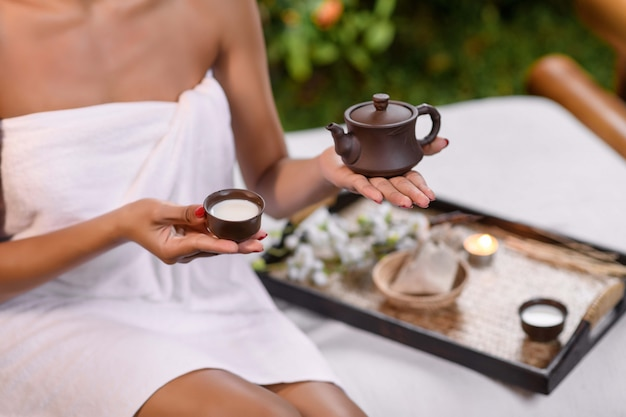 Interracial model posing holding a clay teapot in one hand while in a sudden hand a small clay cup