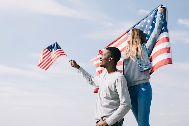 Interracial patriots waving flags as liberty symbol