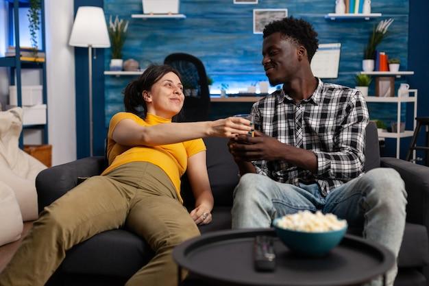 家に座っている妊娠中の異人種間の人々。ソファに横たわっている妊娠中の白人女性のために水のガラスを持って来る子供のアフリカ系アメリカ人の父。赤ちゃんを期待している混血カップル