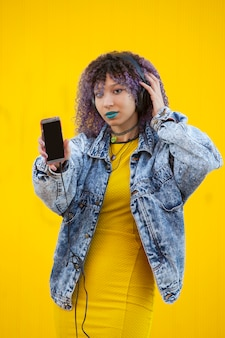Interracial teenager listening to music on a yellow wall