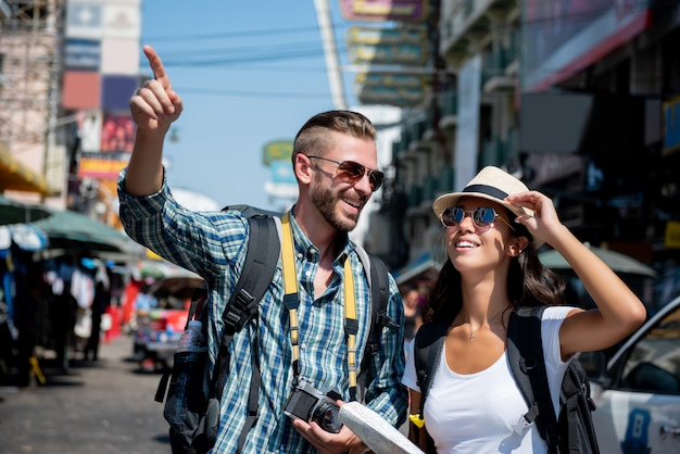 Interracial tourist backpacker couple traveling in bangkok thailand
