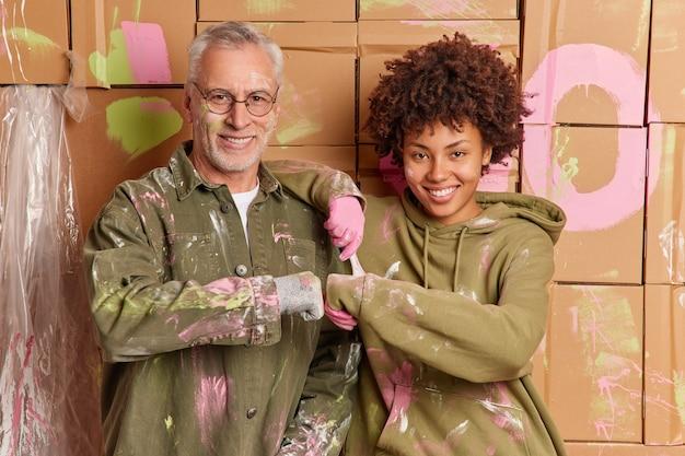 異人種間の女性と男性がフィストバンプを幸せにして家の壁の塗装を終え、幸せな表情で家を一緒にリフォームします。混血の修理工はチームとして働きます。更新と修理の概念
