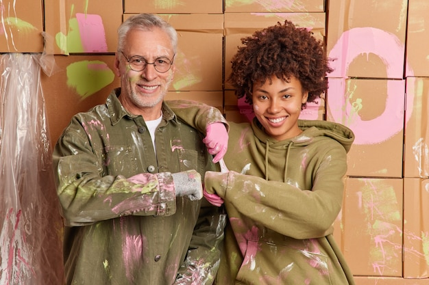 Interracial woman and man make fist bump happy to finish painting walls at home have happy expressions renovate house together. mixed race repairers work as team. renewal and repairing concept