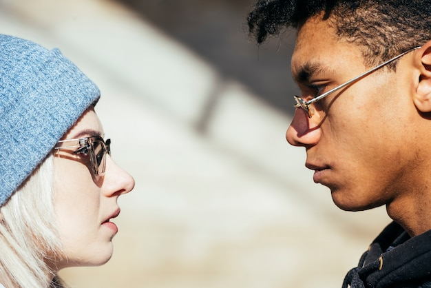 Interracial young couple's face wearing sunglasses looking at each other