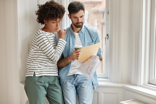 Interracial young woman and man make accounting of their expenses for year, concentrated on paper work