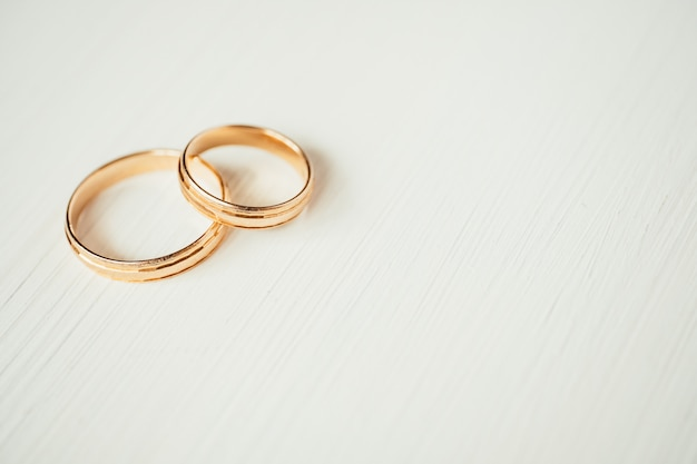 Intersecting wedding gold rings in the left part of white wooden background