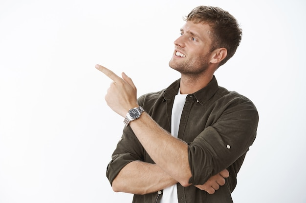 Intersted and curious good-looking male customer with blond hair turning and pointing at upper left corner with intrigued and pleased smile, wanting look closer at product over gray wall