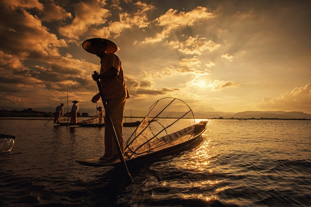 Intha burmese fishermen on boat catching fish traditional at inle lake, shan state, myanmar
