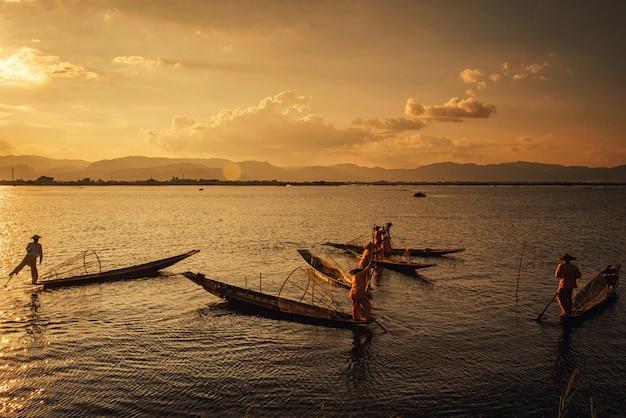 Intha burmese fishermen on boat catching fish traditional at inle lake, shan state, myanmar