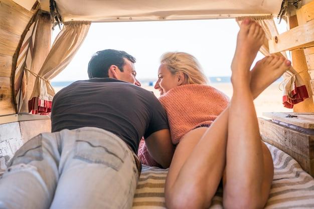 白人の旅行者のカップルが海の前に駐車して自由とカップルのためのさまざまな小さな家を楽しむ、親密で情熱的な代替の古典的な手作りのバンのインテリア。人生を楽しむ