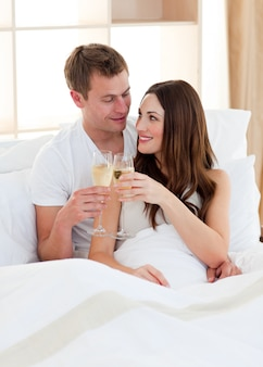 Intimate couple drinking champagne lying in bed