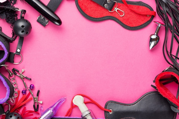 Intimate games. bdsm sex tools dildo vibrator, female panties, gag, nipple clamps, handcuffs, blindfold, buttplug and other on red pink background. free space for your text.
