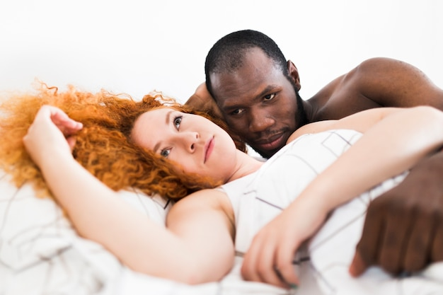 Intimate moment of interracial couple in bed
