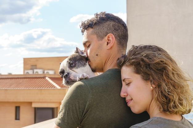 야외에서 개와 키스하는 젊은 부부의 친밀한 순간. 그의 개를 사랑하는 부부의 수평 측면 보기.