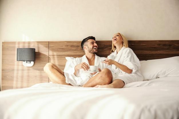 朝のコーヒーとベッドでの親密な瞬間。暖かいローブでコーヒーを飲む2人の恋人のロマンチックなショット。男性と女性は、話している間、幸せで充実しているように見えます。愛に満ち、美しい瞬間を共有する