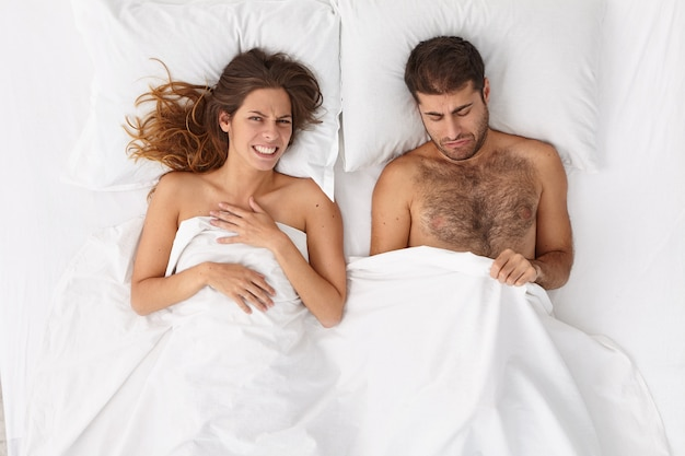 Intimate potency sexual problem and dysfunction. unhappy man has impotency, cannot have sex with wife, needs to take special pills for men, cheerful woman lies under white blanket. top view photo