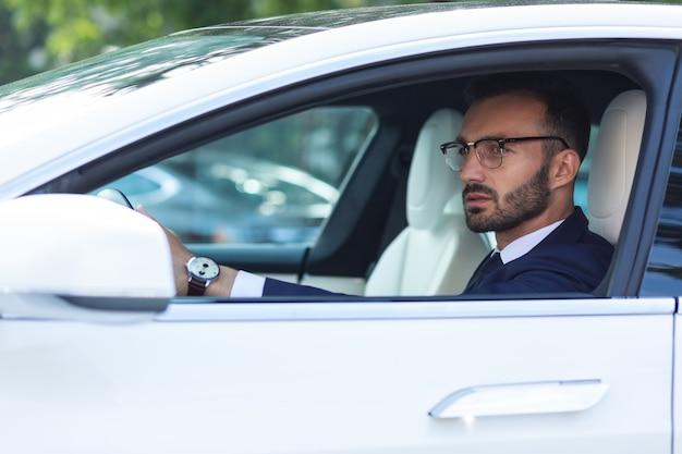 サイドミラーに。車を運転中にサイドミラーを見ているハンドウォッチを身に着けているひげを生やした男