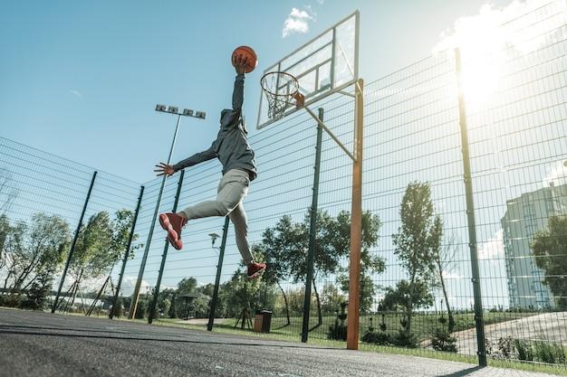 바구니에. 바구니에 공을 던지는 동안 점프 좋은 젊은 남자의 낮은 각도