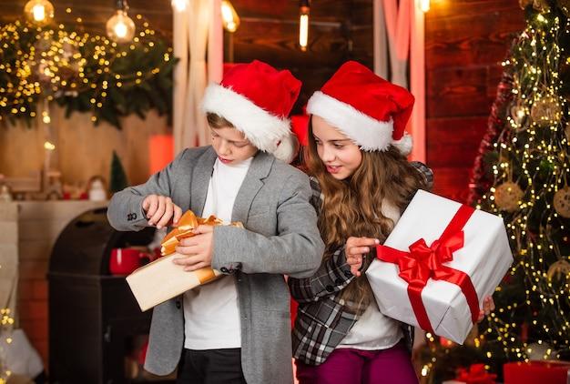 놀라움에 흥미를 느낀다. 축제 분위기 크리스마스 이브입니다. 소년과 소녀 산타 클로스 모자입니다. 가족 크리스마스 전통입니다. 친구는 크리스마스 휴가를 만납니다. 선물 상자와 자매와 형제입니다. 박싱 데이.