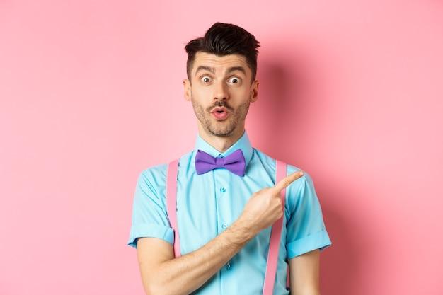 Заинтригованный и удивленный симпатичный парень с усами, показывающий потрясающий промо, с любопытством выглядящий и говорящий «вау», указывая пальцем прямо на логотип, стоящий на розовом фоне.