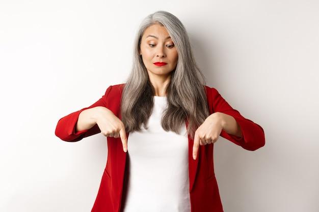 호기심이 아시아 우아한 여자보고 하 고 손가락을 가리키는, 로고를 보여주는, 흰색 배경 위에 빨간색 재킷에 서.