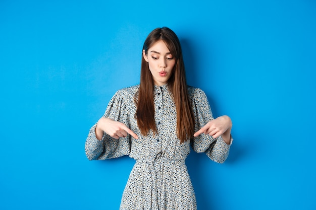 드레스를 입은 호기심 많은 아름다운 소녀가 와우라고 말하며 광고를 내려다보고 아래를 가리키며 관심있는 얼굴, 파란색으로 프로모션을 보여줍니다.