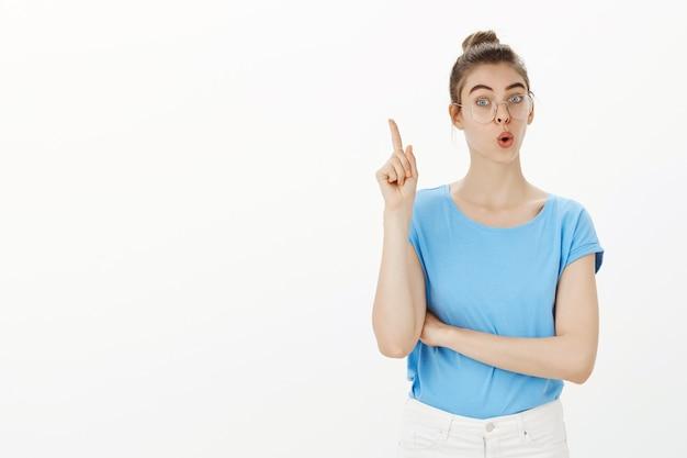 Donna bionda incuriosita che alza il dito, ha suggerimenti, fa un buon piano