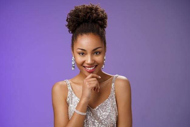 興味をそそられる創造的な若いアフリカ系アメリカ人の邪悪な20代の少女のアフロヘアスタイルは、銀色の豪華なドレスでパーティーをし、あごに触れて神秘的に笑いながら、優れたアイデアに触発された計画、青い背景を持っています。