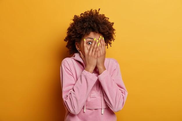 興味をそそられる好奇心旺盛な暗い肌の女性が指をのぞき、手のひらで顔を覆い、身を隠し、何かを恐れ、目を盗み、カジュアルなスウェットシャツを着て、黄色い壁の上で屋内でポーズをとる 無料写真
