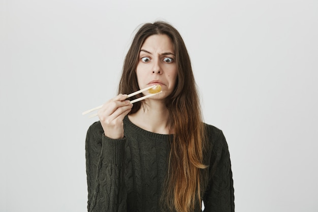 Intrigued funny girl looking at tangerine she holds with chopsticks