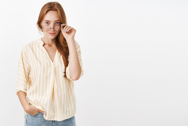 Intrigued smart woman with ginger hair and freckles taking off glasses and looking under rim with curious expression smirking hearing interesting news