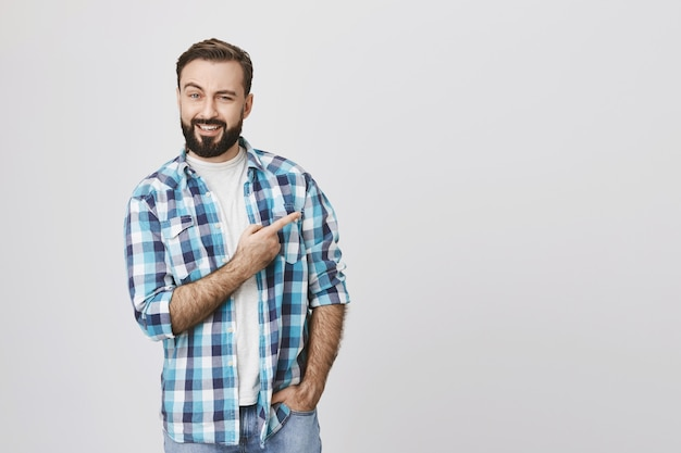Intrigued smiling bearded man pointing finger upper right corner