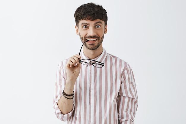 眼鏡をかけて白い壁にポーズをとって興味をそそられるスタイリッシュなひげを生やした男