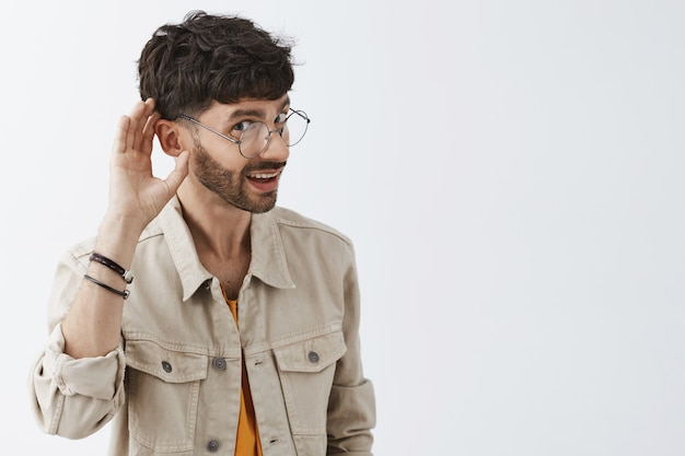 白い壁に向かってポーズをとって興味をそそられるスタイリッシュなひげを生やした男