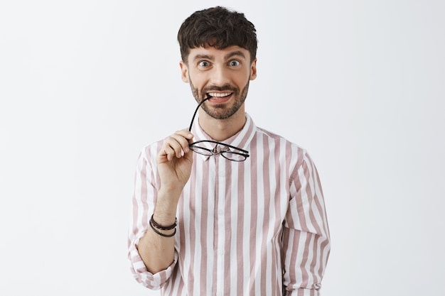 Intrigued stylish bearded guy posing against the white wall with glasses