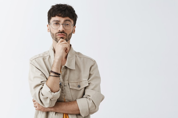 Intrigued stylish bearded guy posing against the white wall