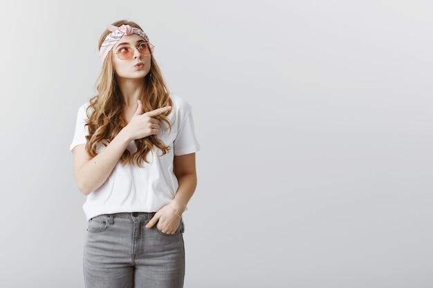 Заинтригованная стильная симпатичная белокурая девушка смотрит и указывает верхний правый угол