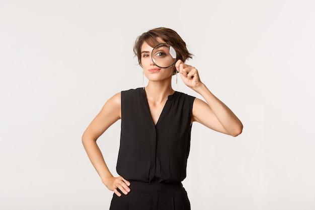 虫眼鏡を通して見ている興味をそそられるスタイリッシュな女性