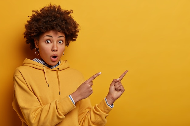 Intrigued surprised adult ethnic woman with afro hairstyle points at upper right corner, shows sign or advertisement banner with great wonder, shocked by high price, dressed in yellow sweatshirt