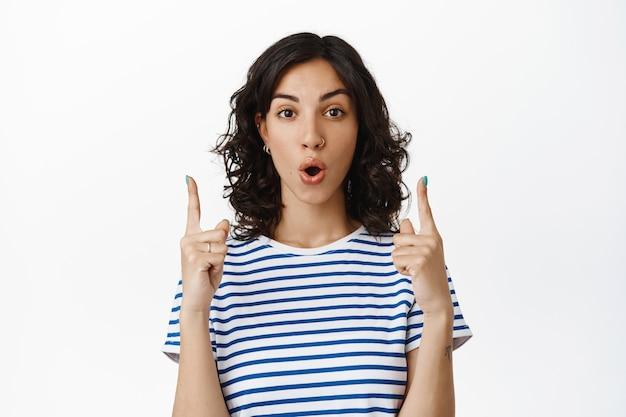 Intrigante giovane donna bruna, ragazza ebrea che punta le dita in alto e dice wow, sembra impressionata ed eccitata con sconti speciali, offerta in negozio, in piedi su bianco