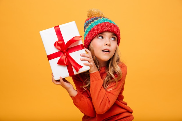 Intrigued young girl in sweater and hat holding gift box and looking away over orange