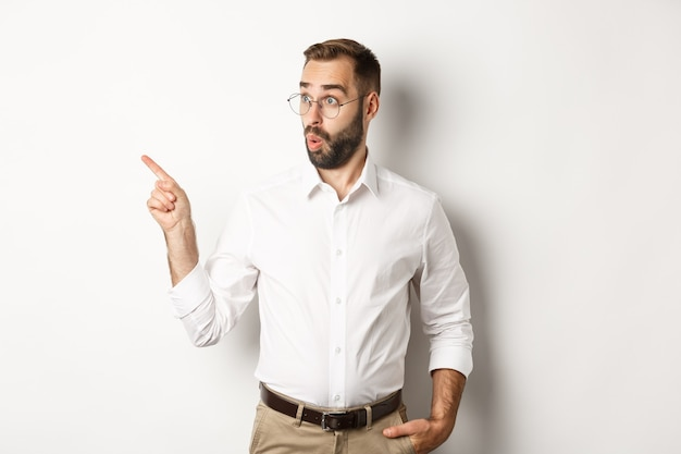 Intrigued young man in glasses pointing finger left, looking at promo offer interested, standing against white background.