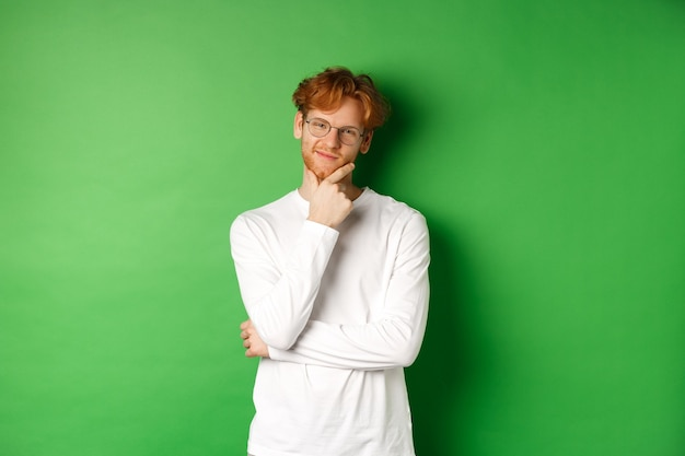 빨간 머리를 가진 호기심이 강한 젊은 남자, 안경을 쓰고, 카메라를 기쁘게 생각하고, 사려 깊고, 생각하고, 녹색 배경 위에 서 있습니다.