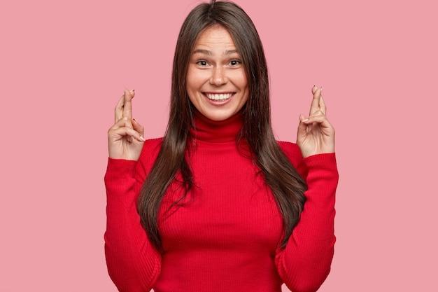 검은 머리카락을 가진 호기심 많은 젊은 여성, 손가락을 계속 교차시키고 긍정적으로 미소 짓고 행운을 믿습니다.