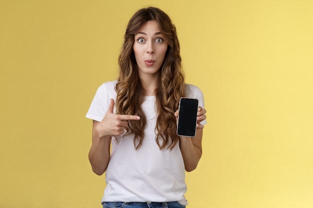 흥미로운 앱 체크 아웃. 호기심 많은 사진 스마트폰 들고 전화 화면 노란색 배경을 가리키는 휴대 전화를 보여주는 열정적인 놀란 매력적인 여자 친구 험담 친구 새 남자 친구